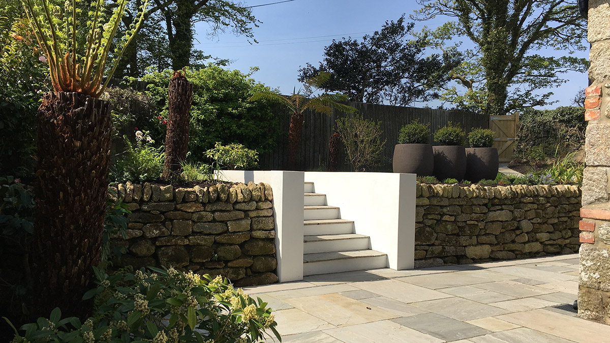 Steps, a stone wall, planting and a paved terrace in a garden