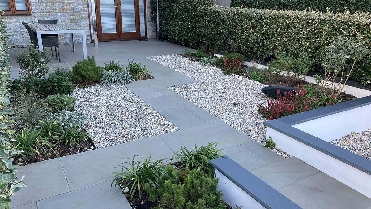 A garden with gravel, a paved path and planting